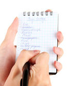 Woman's hand holding a notebook with a shopping list close-up — Foto de Stock