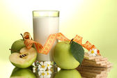 Glass of kefir, apples, crispbreads and measuring tape, on green background — Stock Photo