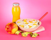 Tasty dieting food, measuring tape and bottle of juice, on pink background — Stock Photo