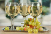 White wine in glass on salver on window background — Stock Photo