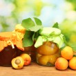 Stock Photo: Canned apricots in a jars and sweet apricots on wooden table on green background