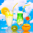 Delicious milk shakes with fruit on table on sky background - Stock Photo