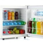 Mini fridge full of bottles of juice, soda and fruit isolated on white — Stock Photo #13484456
