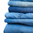 Stock Photo: Many jeans stacked in pile isolated on white