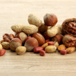 Assortment of tasty nuts on wooden background — Stock Photo #13485458