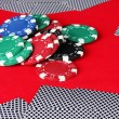 Poker chips and playing cards on a red table — Stock Photo