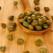 Green capers in wooden spoon on wooden background close-up — Stock Photo