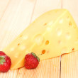 Tasty cheese and berries on wooden background - Stock Photo