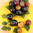 Stock Photo: Rip plums on basket on wooden table