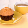 Fresh muffin with tea on wooden background - Stock Photo