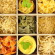 Royalty-Free Stock Photo: Nine types of pasta in wooden box sections close-up isolated on white