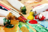Abstract acrylic paint, paint tubes and brushes on wooden palette — Stock Photo