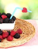 Ripe raspberries and brambles on nature background — Stock Photo