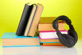 Headphones on books on green background — Stock Photo