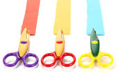 Colorful zigzag scissors with paper strips isolated on white — Stock Photo