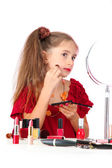 Little girl in her mother's dress, is trying painting her face — Stock Photo