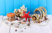 Decor of seashells on wooden table on blue wooden background — Stock Photo