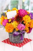 束美丽的鲜艳的花朵与窗口背景上的木桌上的纸笔记 — 图库照片