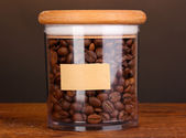 Coffee beans in jar on table on brown background — Stock Photo