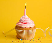 Tasty birthday cupcake with candle, on yellow background — Stock Photo