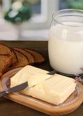Ahşap kutusunda ekmek ve süt ahşap masa üstünde kazanmak çevrili tereyağı — Stok fotoğraf