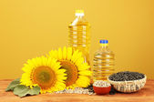 Sunflower oil and sunflower on yellow background — Stock Photo