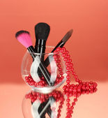 Make-up brushes in a bowl with pearl necklace on red background — Stock Photo
