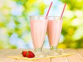 在明亮的背景上的木桌上的草莓奶昔 — 图库照片
