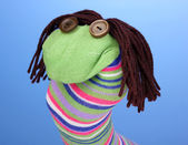 Cute sock puppet on blue background — Stock Photo