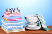 Kitchen towels with dishes on blue background close-up — Stock Photo