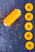 Colorful sewing buttons with thread on jeans closeup — Stock Photo
