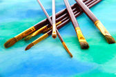 Brushes on bright abstract gouache painted background — Stok fotoğraf