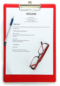Resume with pen and glasses on clipboard, isolated on white — Stock Photo