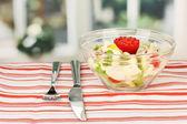 салат из кальмаров с овощами в стеклянную емкость на макро полосатые скатерти — Стоковое фото
