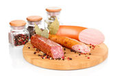 Tasty sausage on chopping board isolated on white — Stock Photo