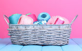 Bright threads in basket on wooden table on pink background — Stock Photo