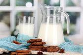 Jarra y vaso de leche con galletas en punto de crewnecks en madera tabl — Foto de Stock