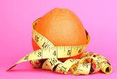 Naranja con longímetro sobre fondo rosa — Foto de Stock