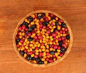 Kolorowe jagody jesienią na maty wiklinowe na drewniane tło zbliżenie — Zdjęcie stockowe
