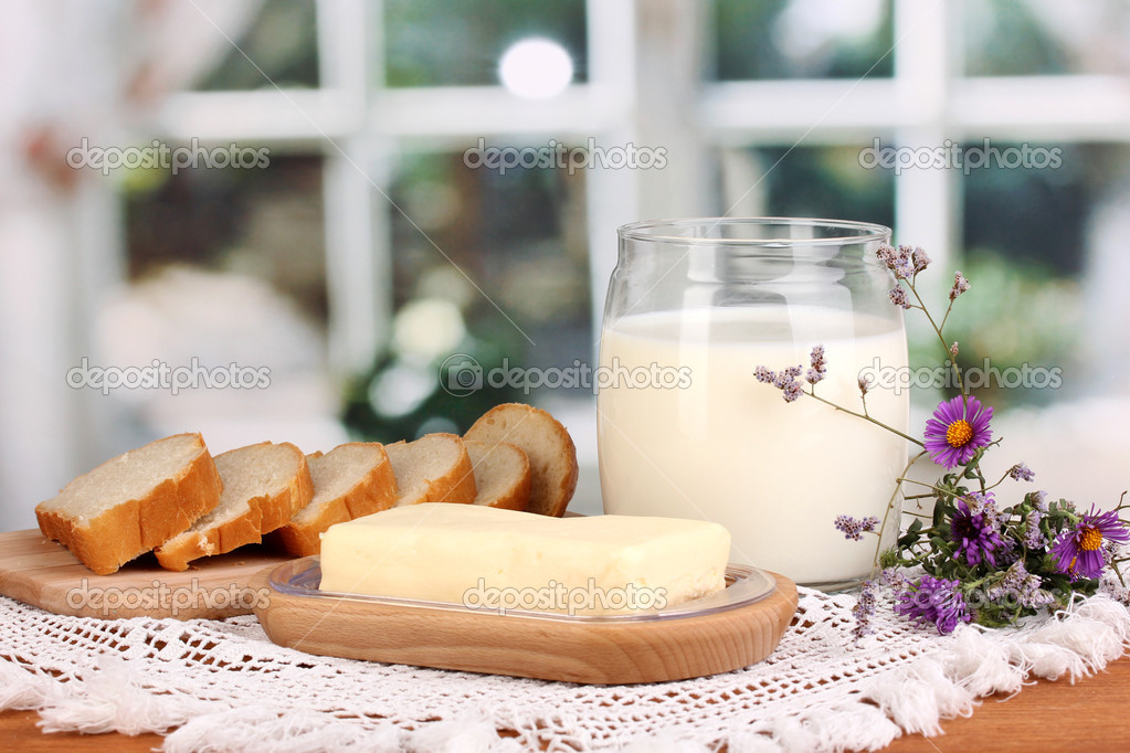Butter on wooden holder surrounded by bread and milk on window background — Stock Photo #13485411