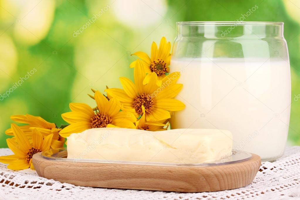 Butter on wooden holder surrounded by flowers and milk on natural background close-up — Stock Photo #13485417