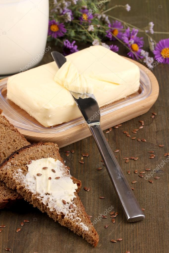 Butter on wooden holder surrounded by bread and milk on wooden table close-up — Stock Photo #13485420
