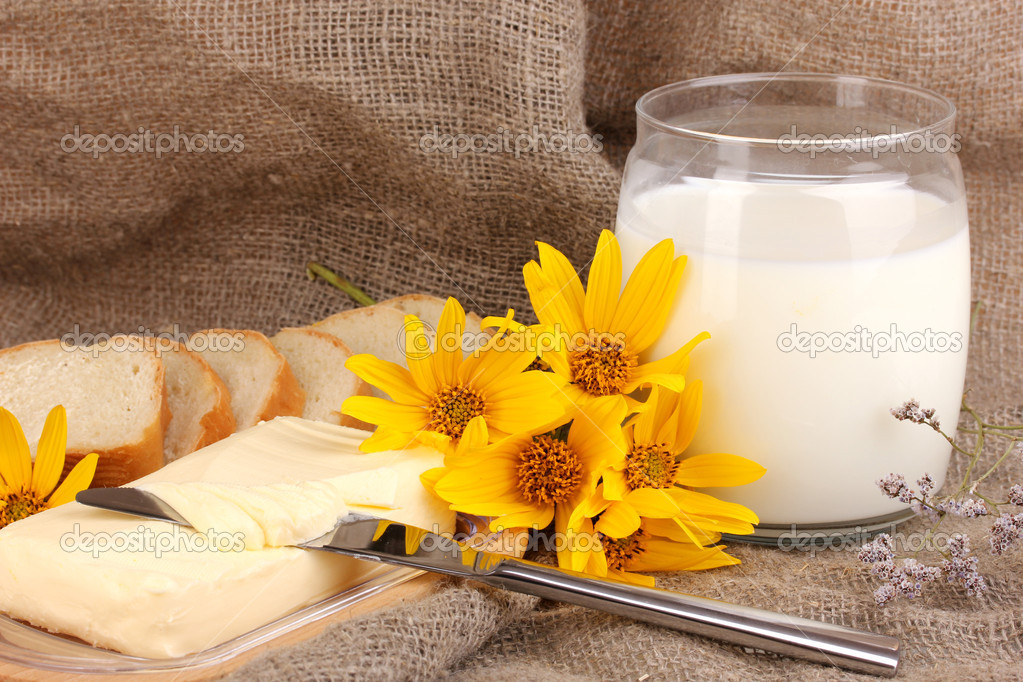 Butter on wooden holder surrounded by bread and milk on sacking background — Stock Photo #13485422