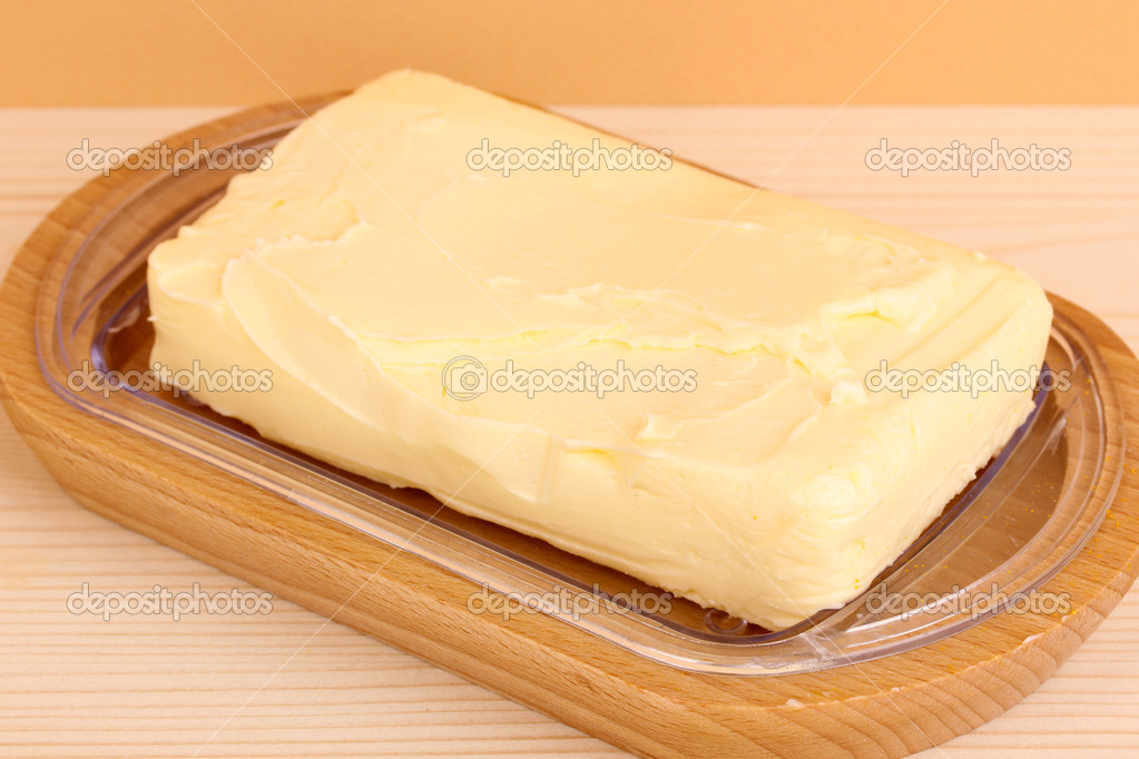Butter on wooden holder on wooden table on beige background — Stock Photo #13485426