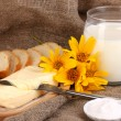 Butter on wooden holder surrounded by bread and milk on sacking background — Stock Photo #13508977