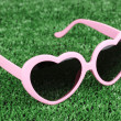 Pink heart-shaped sunglasses on green grass — Stock Photo