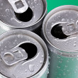 Stock Photo: Aluminum cans with water drops on green background