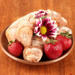 Fresh bagels with strawberry in the plate on wooden background close-up — Stock Photo