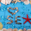 Stock Photo: Word seand decor of seashells close-up on blue wooden table