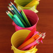 Colorful pencils and felt-tip pens in color pails close-up on wooden table — Stock Photo #13508619